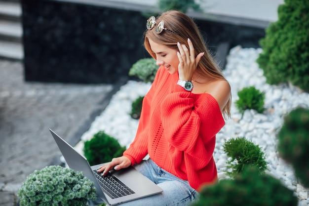 Junge studentin, blonde frau im roten hemd mit laptop, die in der städtischen straße stillsteht.