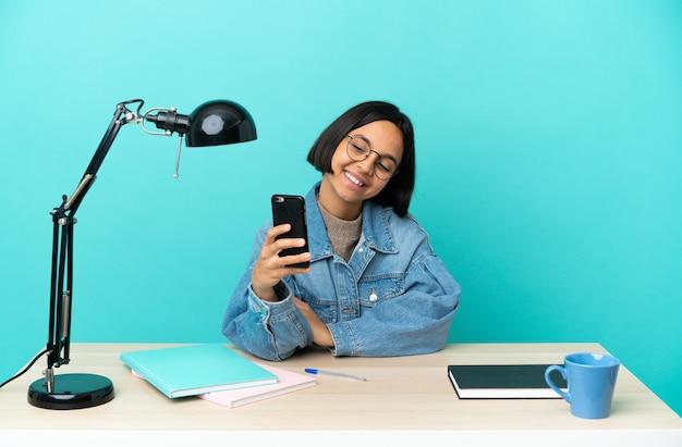 Junge studentin der gemischten rasse, die auf einem tisch studiert, der ein selfie macht