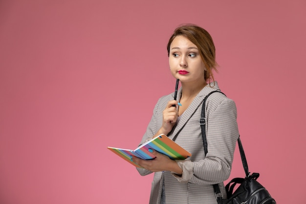 Junge studentin der vorderansicht im grauen mantel, der das heft mit dem denkenden ausdruck auf dem rosa hintergrundunterrichtsuniversitätshochschulstudium aufwirft