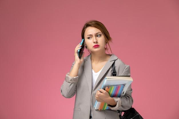 Junge studentin der vorderansicht im grauen mantel, der hält bücher hält, die am telefon auf dem rosa hintergrundlektionsuniversitätshochschulstudienbuch sprechen