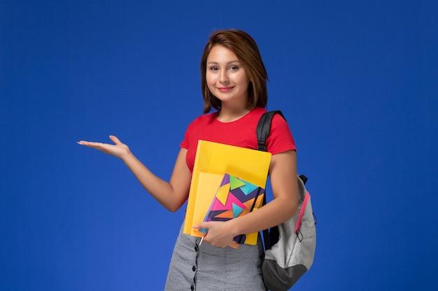 Junge studentin der vorderansicht im roten hemd, das rucksack hält, der dateien und heft auf dem blauen hintergrund hält.