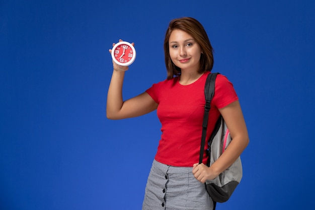 Junge studentin der vorderansicht im roten hemd, das rucksack hält uhren auf dem hellblauen hintergrund trägt.