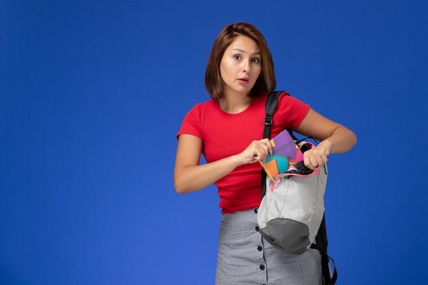 Junge studentin der vorderansicht im roten hemd, das rucksack trägt und heft auf dem hellblauen hintergrund hält.
