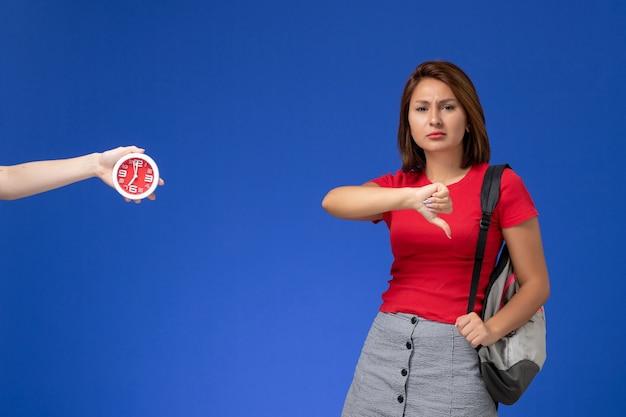 Junge studentin der vorderansicht im roten hemd, das rucksack trägt, zeigt unähnliches zeichen auf hellblauem hintergrund.