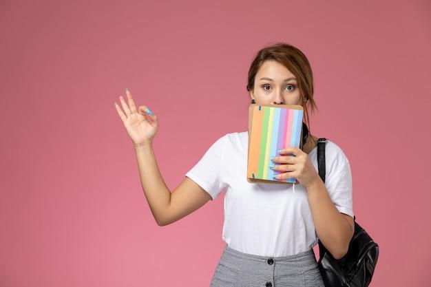 Junge studentin der vorderansicht im weißen t-shirt, das hefte mit überraschtem ausdruck auf dem rosa hintergrundlektions-universitätsuniversitäts-studienbuch hält