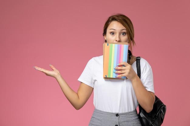 Junge studentin der vorderansicht im weißen t-shirt, das hefte mit überraschtem ausdruck auf rosa hintergrundlektionsuniversitätsuniversitäts-studienbuch hält