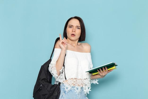 Junge studentin der vorderansicht in den weißen jeans des weißen hemdes und der schwarzen tasche, die das heft auf der studentin des blauen raums liest