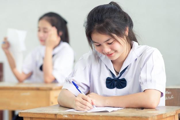 Junge studentin des lächelns, die prüfung ohne druck liest und schreibt.