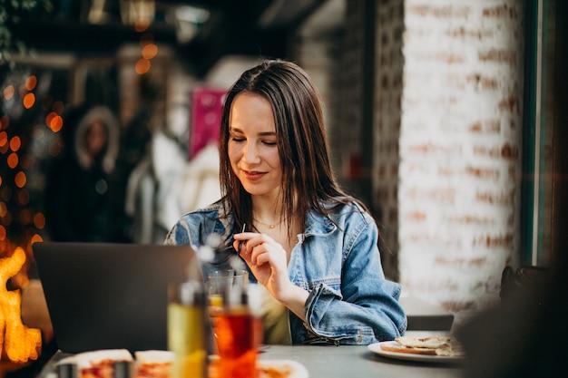 Junge studentin, die an laptop in der bar arbeitet und pizza isst