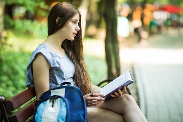 Junge studentin, die auf bank sitzt und buch im park liest
