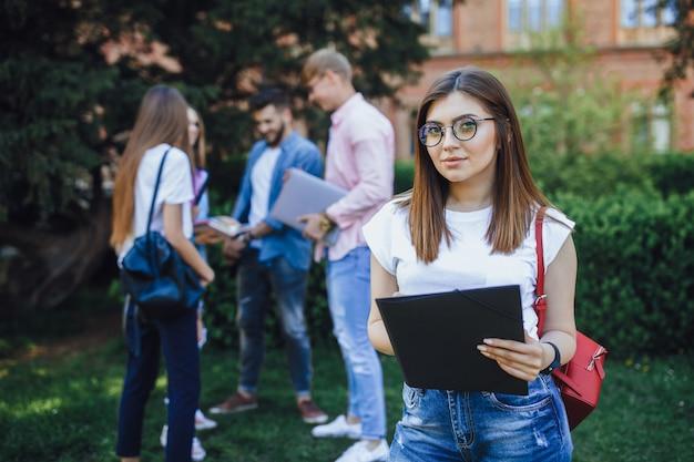 Junge studentin, die auf einem campus steht und lächelt.