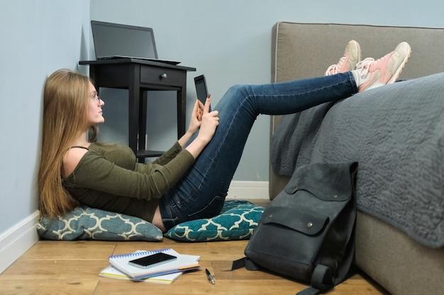 Junge studentin, die digitalen tablet-pc liest, online-bildung, fernunterricht. kluges mädchen mit brille, die auf boden sitzt