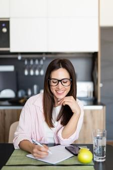Junge studentin, die ihre hausaufgaben zu hause in der küche macht