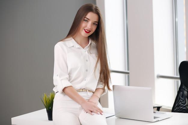 Junge studentin, die im büro sitzt und probleme löst