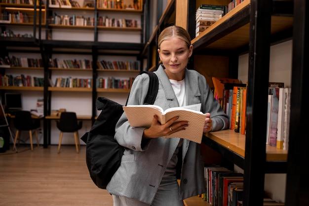 Junge studentin, die in der bibliothek liest
