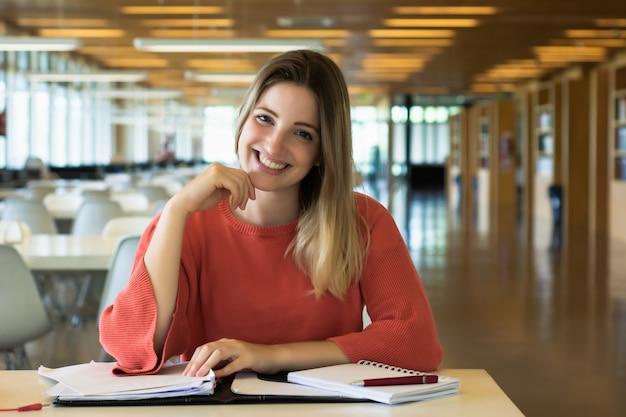 Junge studentin, die in der bibliothek studiert.