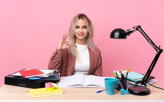 Junge studentin, die in einer tabelle arbeitet, die ein ok-zeichen mit den fingern zeigt