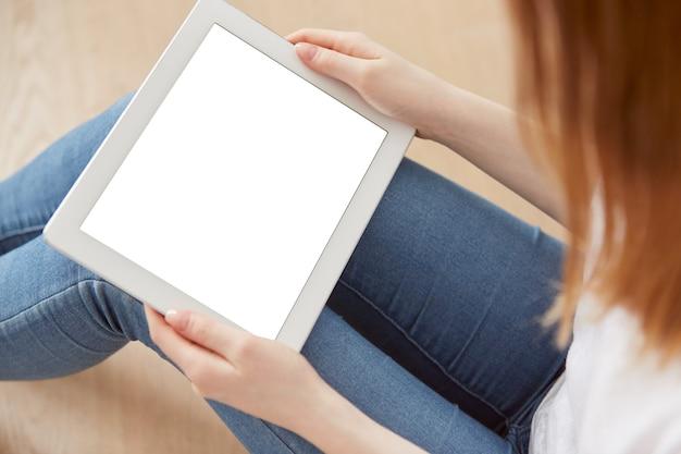 Junge studentin, die in einer universitätserholungshalle unter verwendung des touchpads sitzt
