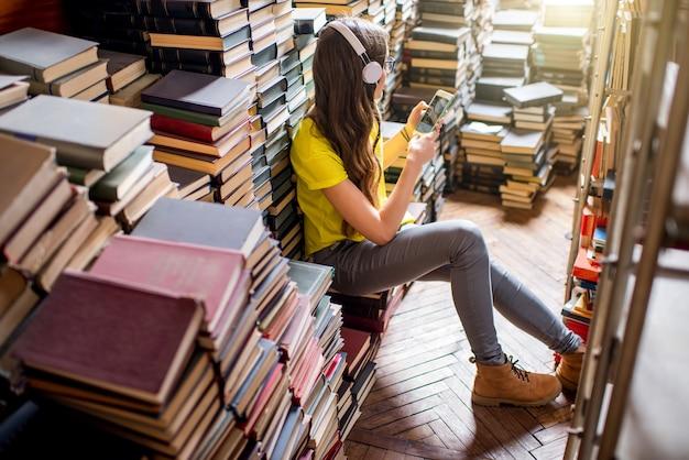 Junge studentin, die musik hört, die auf dem bücherhaufen in der alten bibliothek sitzt