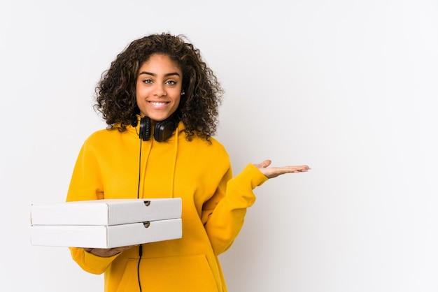 Junge studentin, die pizzen hält, die einen kopienraum auf einer handfläche zeigen und eine andere hand auf taille halten