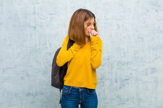 Junge studentin, die sich mit halsschmerzen und grippesymptomen krank fühlt und mit dem mund hustet, der gegen schmutzwandwand bedeckt wird
