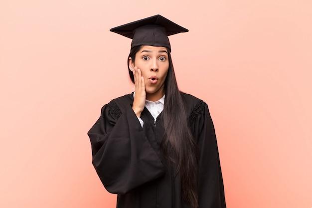 Junge studentin, die sich schockiert und erstaunt fühlt, gesicht ungläubig mit weit geöffnetem mund an hand zu halten
