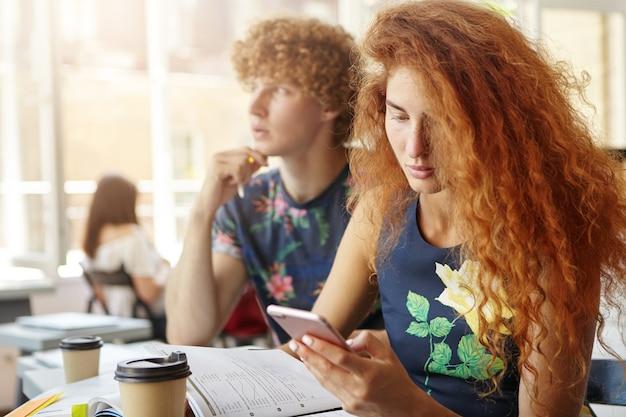 Junge studentin, die smartphone hält, das nach informationen im internet sucht
