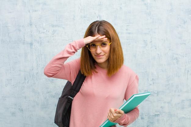 Junge studentin, die verwirrt und erstaunt schaut, mit der hand über stirn weit weg schauend, beobachtend oder suchend gegen schmutzwandhintergrund