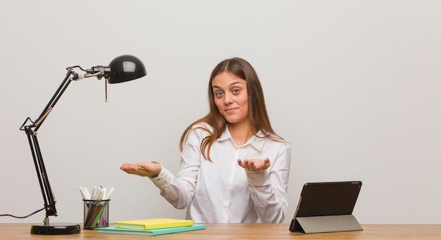 Junge studentin, die verwirrt und zweifelhaft an ihrem schreibtisch arbeitet