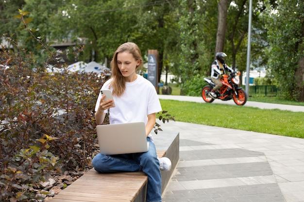 Junge studentin, die während der zeit zum e-learning im park auf der bank mobile sms-nachrichten sendet