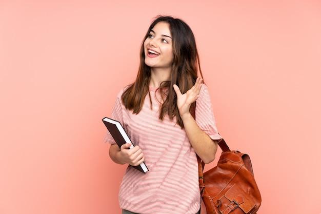 Junge studentin, die zur universität über rosa wand mit überraschendem gesichtsausdruck geht
