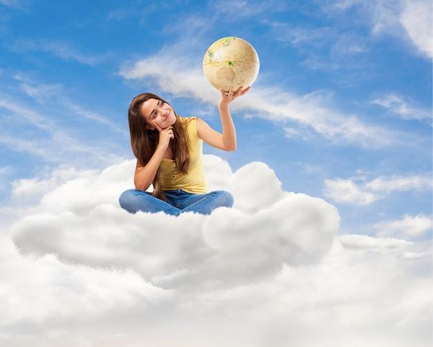 Junge studentin frau, die ihre weltkugel sucht auf einer wolke sitzt
