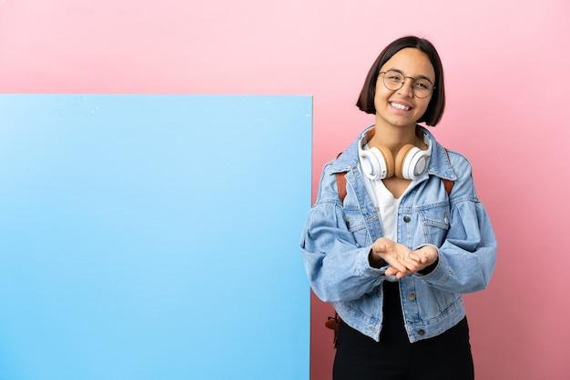 Junge studentin gemischte rassenfrau mit einem großen banner über isoliertem hintergrund, der imaginären copyspace auf der handfläche hält, um eine anzeige einzufügen