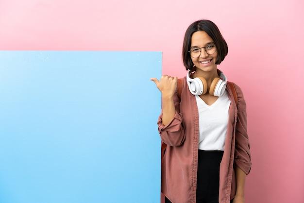Junge studentin gemischte rassenfrau mit einem großen banner über isoliertem hintergrund, der zur seite zeigt, um ein produkt zu präsentieren