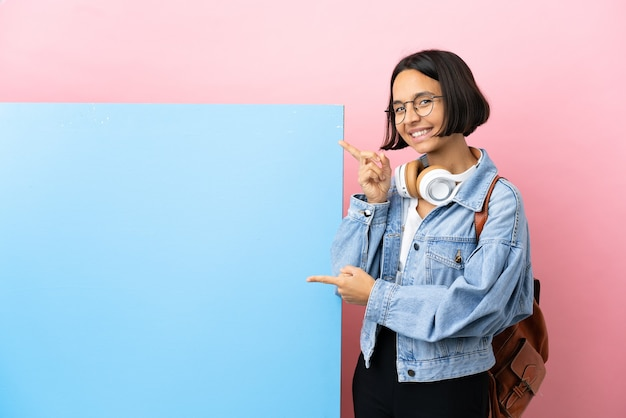 Junge studentin gemischte rassenfrau mit einem großen banner über lokalisiertem hintergrund, der finger zur seite zeigt und ein produkt präsentiert