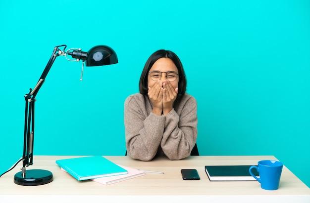 Junge studentin gemischter abstammung, die auf einem tisch glücklich und lächelnd studiert und den mund mit den händen bedeckt?