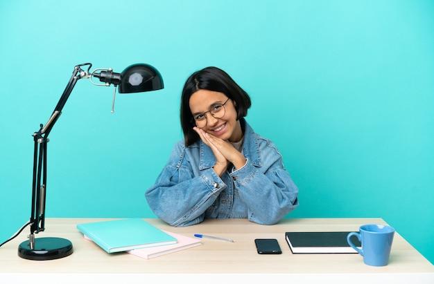 Junge studentin gemischter abstammung, die auf einem tisch studiert, hält die handfläche zusammen. person fragt nach etwas