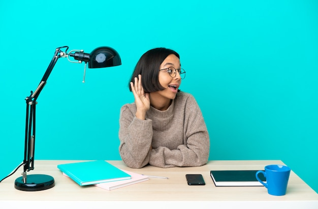Junge studentin gemischter abstammung, die auf einem tisch studiert und etwas hört, indem sie die hand auf das ohr legt