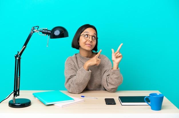 Junge studentin gemischter abstammung, die auf einem tisch studiert und mit dem zeigefinger zeigt, eine großartige idee