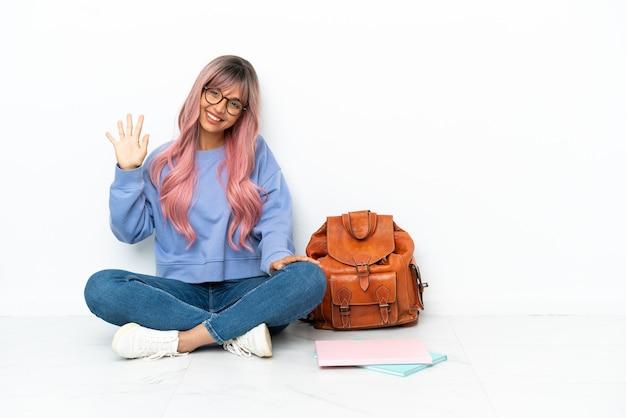 Junge studentin gemischter abstammung mit rosa haaren sitzt auf dem boden isoliert auf weißem hintergrund und zählt fünf mit den fingern