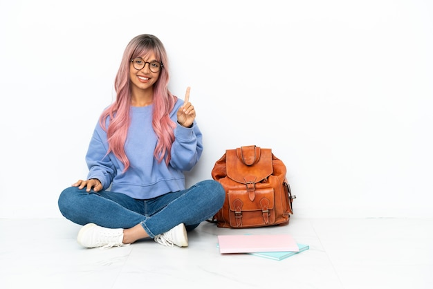 Junge studentin gemischter abstammung mit rosa haaren sitzt auf dem boden isoliert auf weißem hintergrund und zeigt und hebt einen finger