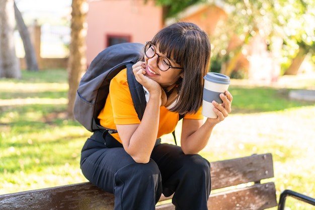 Junge studentin gewinnt einen park mit einem kaffee zum mitnehmen