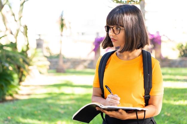 Junge studentin gewinnt einen park mit einem notebook