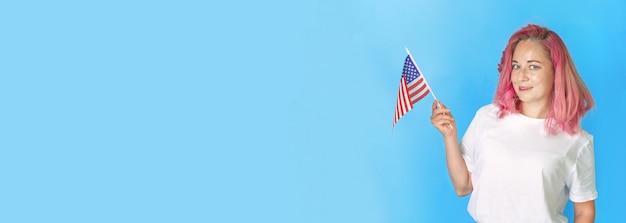 Junge studentin hält amerikanische kleine flagge auf blauem hintergrund, glückliche frau hält usa-flagge. breites banner