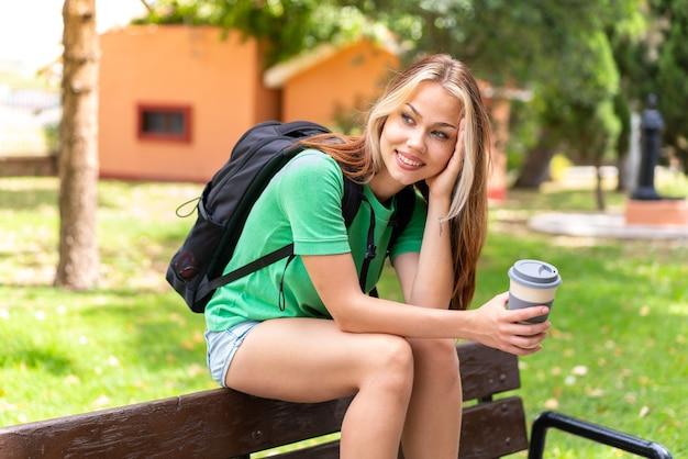 Junge studentin im freien, die einen kaffee zum mitnehmen hält