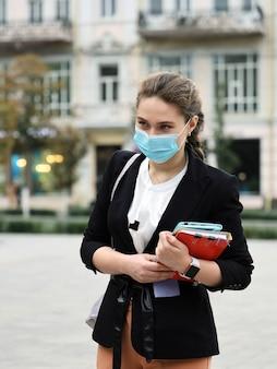 Junge studentin in anzug und schutzmaske mit notizbuch in ihren händen geht die stadtstraße entlang