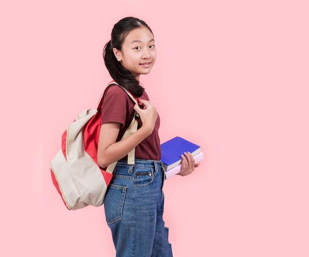 Junge studentin in der highschool, die an der rosa wand der kamera lächelt