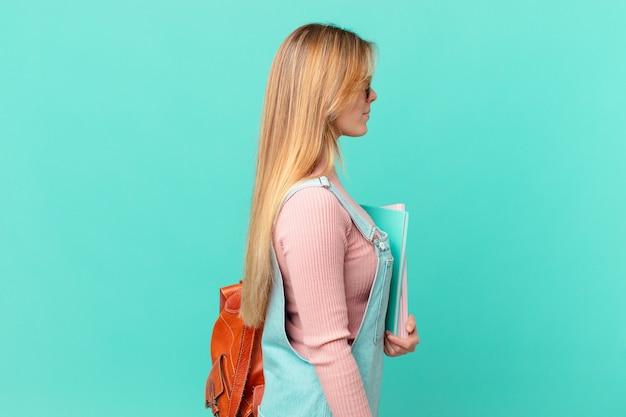 Junge studentin in der profilansicht, die nachdenkt, sich vorstellt oder träumt