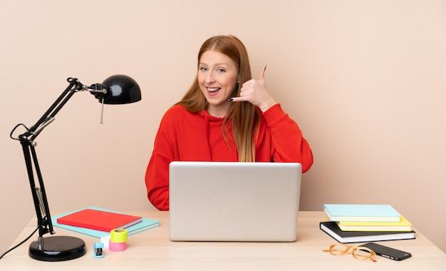Junge studentin in einem arbeitsplatz mit einem laptop, der telefongeste macht. rufen sie mich zurück zeichen