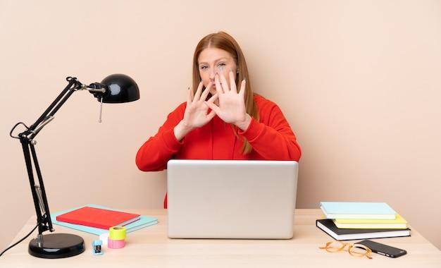 Junge studentin in einem arbeitsplatz mit einem laptop nervös streckenden händen nach vorne